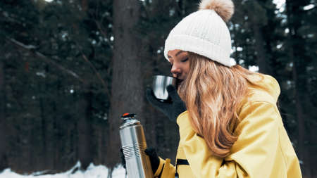 A girl in a yellow jacket pours tea from a vacuum flask in the winter in the forest