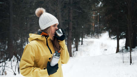 A girl in a yellow jacket drinks tea from a vacuum flask in the winter in the forest