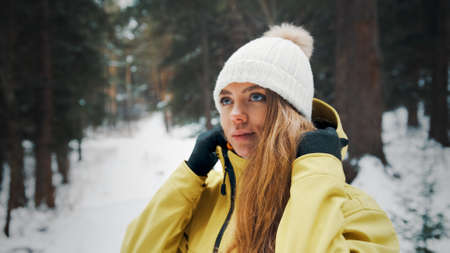 Girl in a yellow jacket puts on a hoodie in the forest in winter