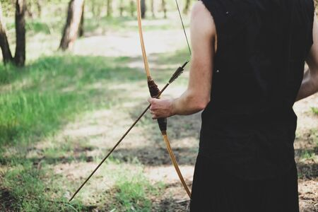 A man shoots a bow in the open air. The near foreshortening. An arrow is pulled over the bow.