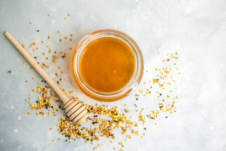 Honey and honey spoon on a light background. Sweet honey in a jar, pollen scattered near the jar. Place for text