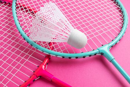 Badminton rackets and shuttlecock on a bright pink background. The concept of equipment for amateur sports. Minimalism. Stock Photo