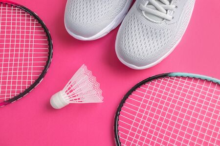 Sneakers, badminton rackets and shuttlecock on a bright pink background. The concept of equipment for amateur sports. Minimalism.