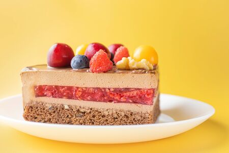 A piece of chocolate berry cake in a white plate on a yellow background. The concept of homemade food, sweets. Minimalism.