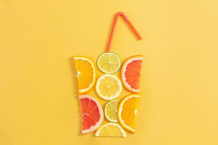 Creative concept of citrus juice, smoothie, summer drinks. Slices of orange, grapefruit, lemon and lime are folded in the shape of glass on yellow background. Top - red, yellow, green, orange tubules.