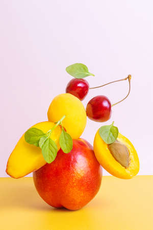 Creative bright composition of apricots, nectarines and cherries. The concept of fruits and berries, vitamin healthy food, vegetarianism. Yellow and orange shades, levitation. Stock fotó