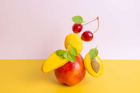 Creative bright composition of apricots, nectarines and cherries. The concept of fruits and berries, vitamin healthy food, vegetarianism. Yellow and orange shades.