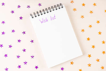 Spiral notebook lies on light background. On white sheet of paper, inscription in purple marker - Wish List. Around - purple and orange rhinestones in shape of stars. Top view, flat lay, copy space. Imagens