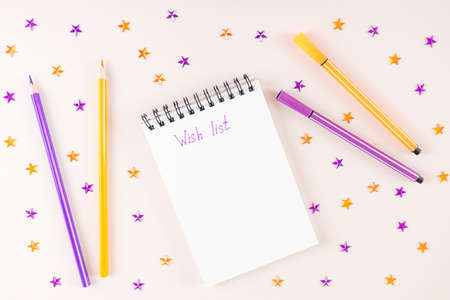 Spiral notebook on light background. On white sheet of paper inscription - Wish List. Around - purple and orange rhinestones in shape of stars, pencils anm markers. Top view, flat lay, copy space.