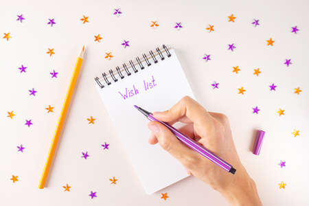 Spiral notebook and female hand with purple marker. On white sheet of paper inscription - Wish List. Around - purple and orange rhinestones in shape of stars, pencil. Top view, flat lay, copy space. Imagens