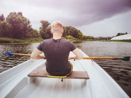 A blond Caucasian man in a gray T-shirt sits in a boat with his back to the frame and paddles on the river. Cloudy stormy sky. 스톡 콘텐츠