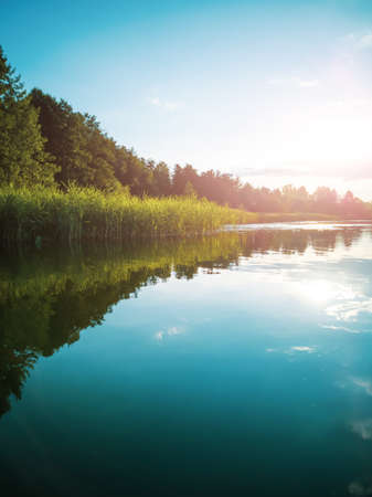 Summer landscape: the sky with clouds and the forest on the horizon are reflected in the clear water of the lake. Copspace. The concept of a relaxing holiday, the beauty of nature.