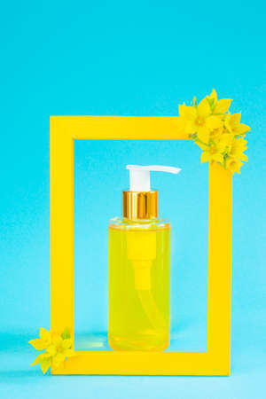 Cosmetic bottle with a dispenser with natural oil is framed by a yellow frame. There are yellow flowers. Stylish concept of organic essences, beauty and health products. Minimalism, copy space.