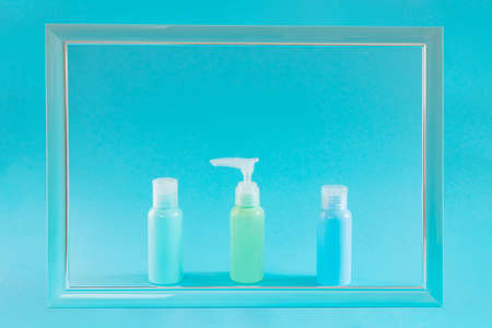 Blue cosmetic bottles on a blue background in a frame. Stylish concept of organic essences, beauty and health products. Copy space, minimalism. Foto de archivo