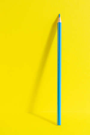 Back to school. A blue pencil stands on a yellow background. Creative minimalistic concept of children's creativity, drawing.