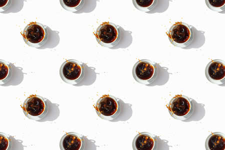 Black coffee in white cups, top view. Sugar lumps are thrown into the cup, spectacular splashes are spilling out of the cup. White background. International coffee day. 免版税图像