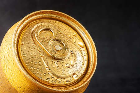 Closed tin can, close-up top view. Golden color, water drops on the can.