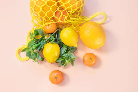 Oranges, tangerines, lemons in a yellow string bag. Citruses, vitamin C. Sustainability, zero waste, plastic free concept, vegetarianism, healthy food. Top view.