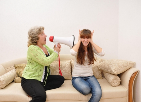 generation gap: mother shouting at her doughter with a megaphone
