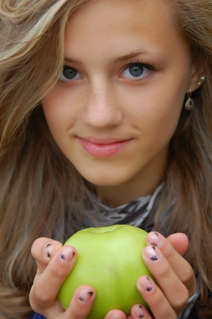 a pretty teenage girl holding a green apple photo