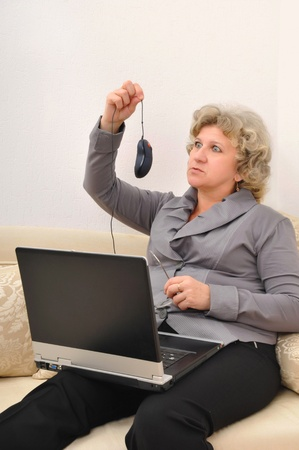 portrait of a middle-aged woman with a laptop seating on the sofa photo