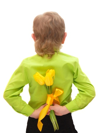a small boy holding yellow tulips behind his back isolated on white photo