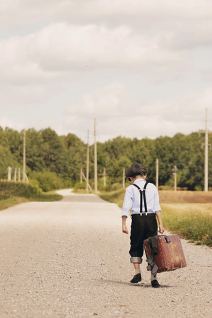 young boy sadly walking away by a field road with a suitcase filled with all his stuff