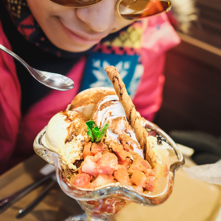 Young women are enjoying a beautiful ice cream parfait in a dessert shop during a trip Stock Photo