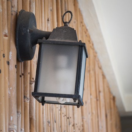 Old style black Street lamp on bamboo wall photo