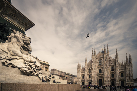 Lion statue in Milano, doves and cathedral, vintage style photo