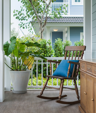wooden rocking chair on front porch with pillow and planter photo