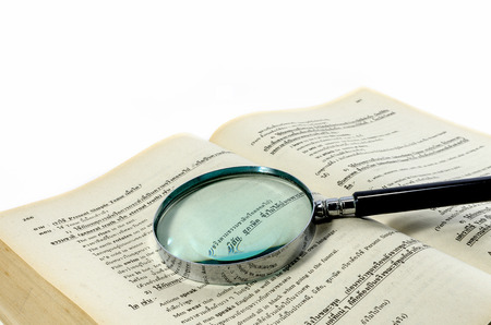 Magnification glass over a opened old book on white background