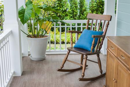 silla de madera: mecedora de madera en el porche con una almohada Foto de archivo