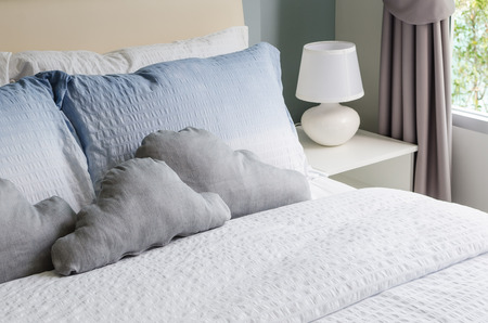 bed and pillows with white lamp on table photo