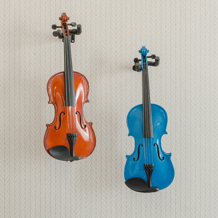 violins: blue and brown violins hang on beige wall Stock Photo