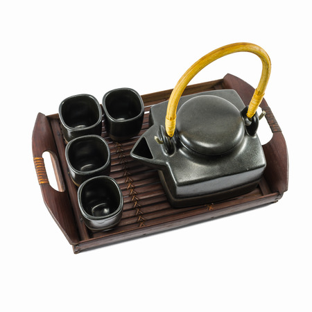 trivet: Chinese black teapot and teacups on the wooden trivet isolated on white