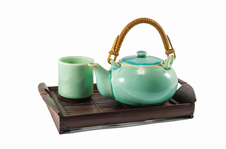 trivet: Chinese green teapot and teacups on the wooden trivet isolated on white
