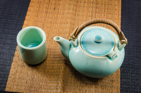 trivet: Chinese green teapot and teacups on the wooden trivet