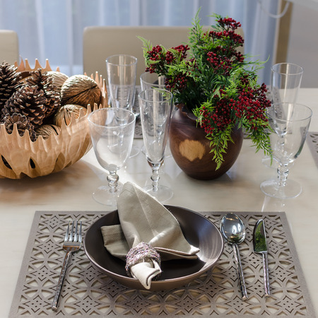 earth tone table set with flower in dinning room at home photo