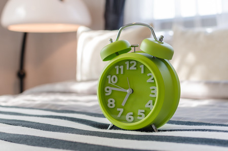 green alarm clock on bed photo