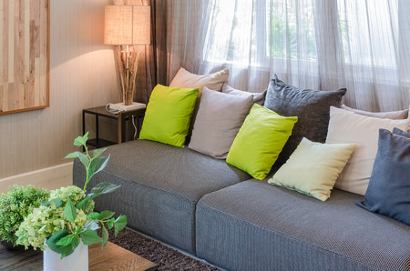green sofa: grey sofa and green pillows in living room at home