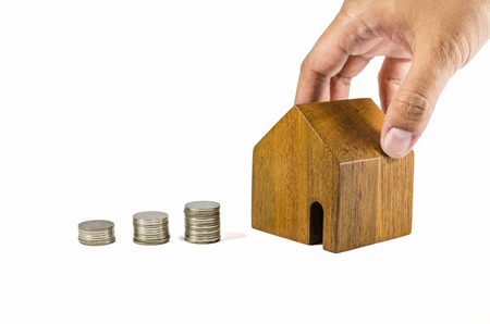 dearness: hand try to pick up wooden toy house with coins concept of dearness of habitation on white background