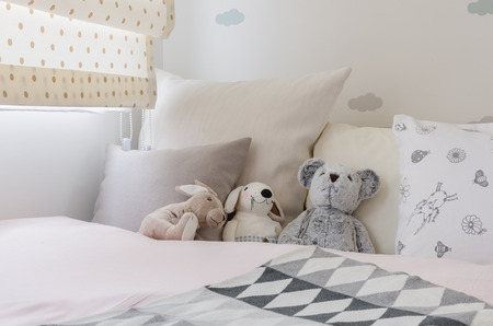 kid room with dolls and pillows on bed at home photo