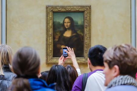 """Frankreich, Paris - 14. April: Unidentified Touristen nehmen Sie Fotos von Leonardo da Vincis """"Mona Lisa"""" mit dem Handy am Louvre-Museum, 14. April 20013 in Paris, Frankreich. Das Gemälde ist eines der weltweit berühmtesten Kunstwerke Standard-Bild - 34860569"""