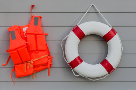 life vest and life belt on wooden wall photo