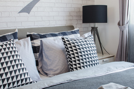 modern bedroom with black and white pillows and black lamp at home photo
