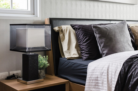 modern grey bedroom with wooden nightstand and lamp at home Фото со стока