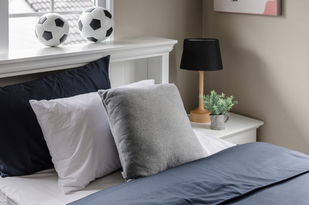 modern white bed with pillow and  football on top at home photo