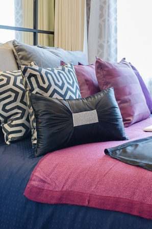 multicolor pillows on bed in bedroom photo