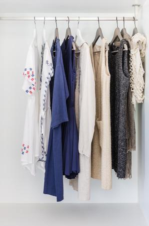 row of cloth hanging on coat hanger in wardrobe